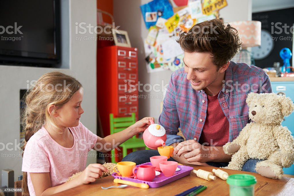 Father Playing Game With Daughter And Toys In Bedroom stock photo