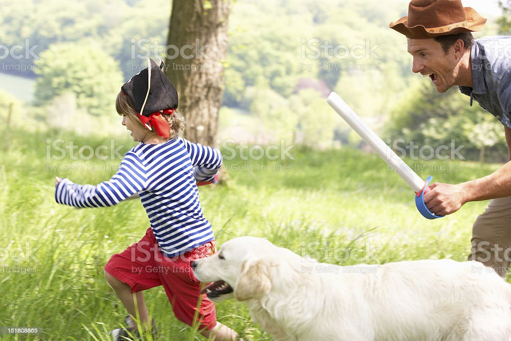 Father Playing Game With Son And Dog In Field stock photo