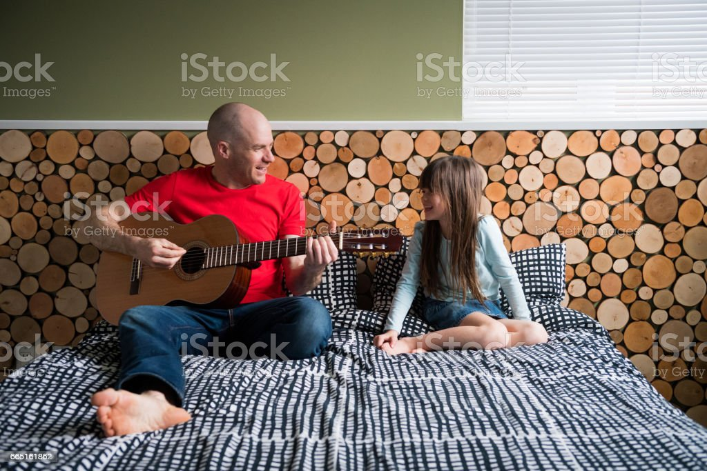 Father playing guitar for his daughter stock photo
