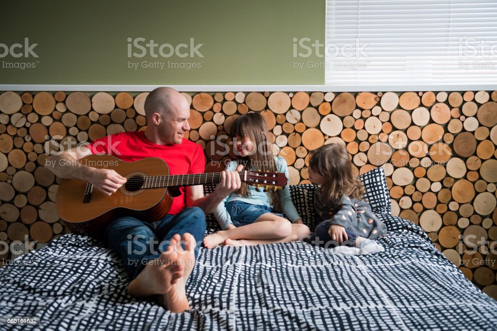 Father playing guitar for his daughters stock photo