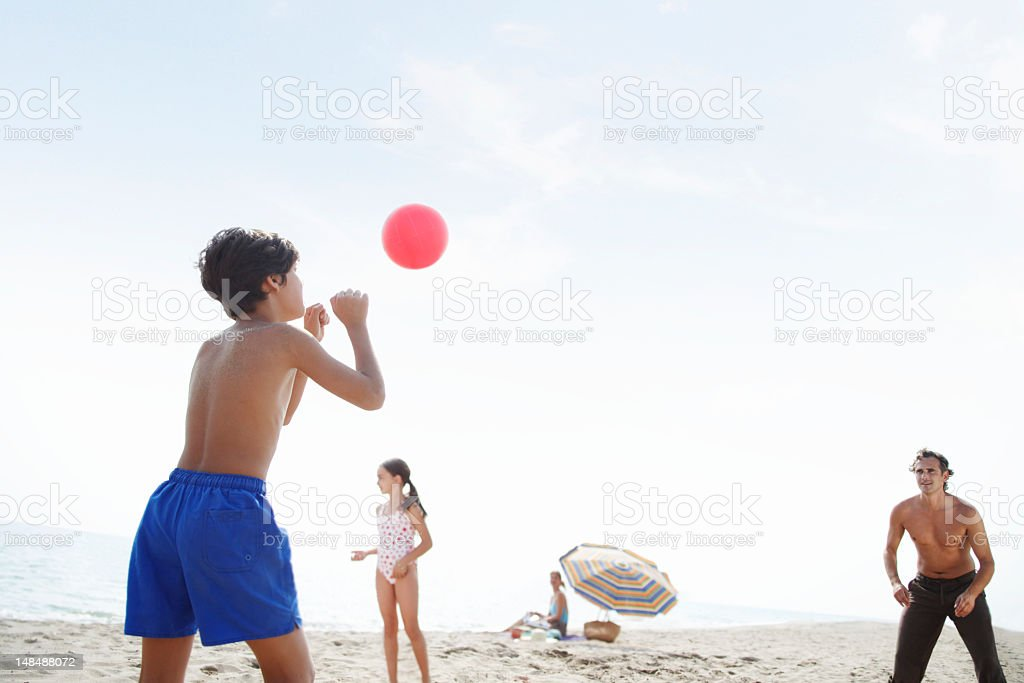 Father playing volleyball on beach with son and daughter (7-9) royalty-free stock photo