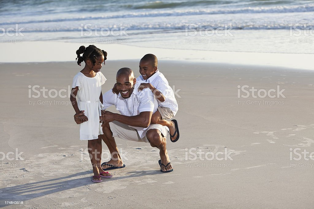 Father playing with children on beach stock photo