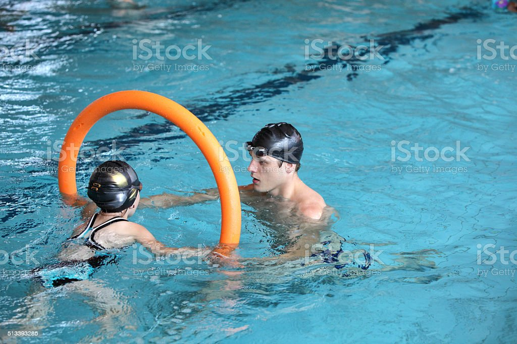 father playing with daughter in swimming pool stock photo
