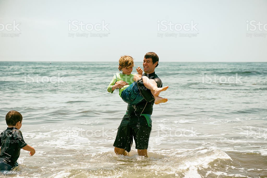 Father playing with his children in the ocean stock photo