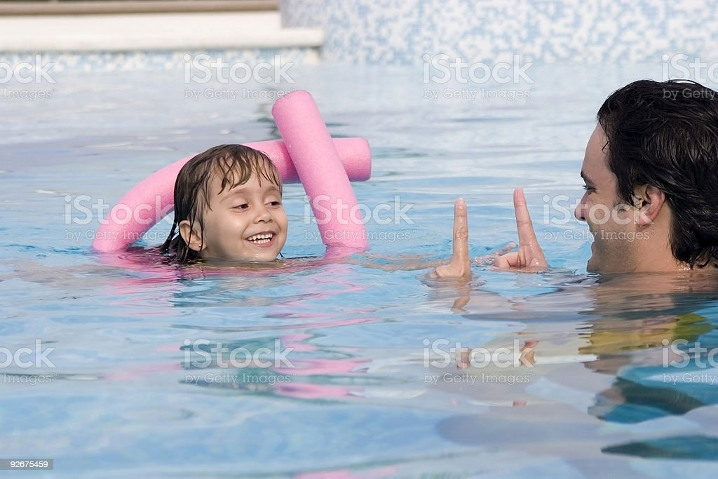 Father playing with his daughter in swimming pool royalty-free stock photo