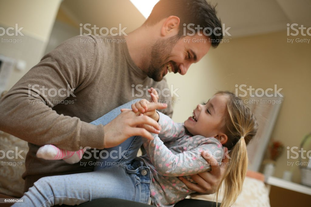 Father playing with his daughter. stock photo