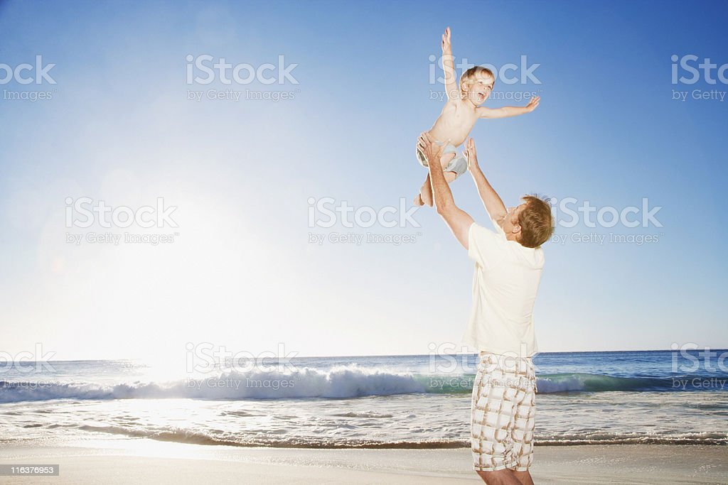 Father playing with son on beach royalty-free stock photo
