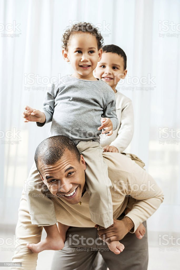 Father playing with sons at home. royalty-free stock photo