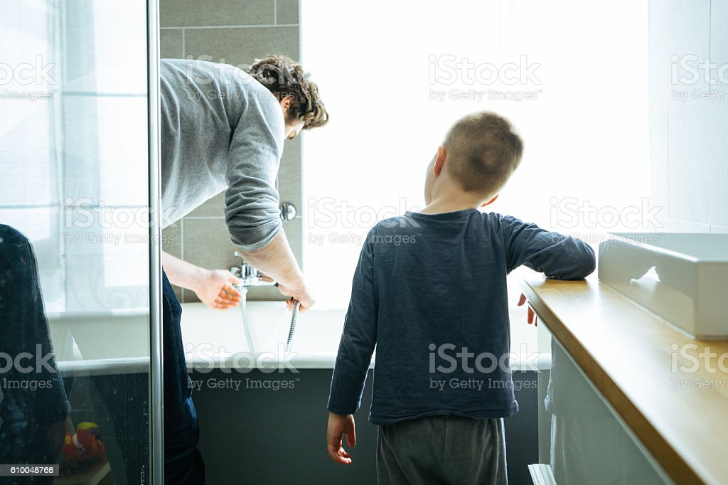 Father preparing the bathtub for his son stock photo