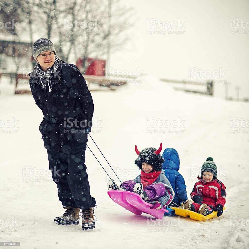Father pulling kids on sleds. royalty-free stock photo