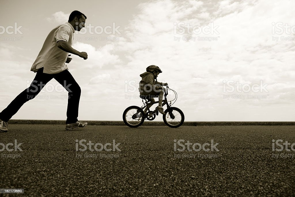 Father pursuing young cyclist learning to ride stock photo