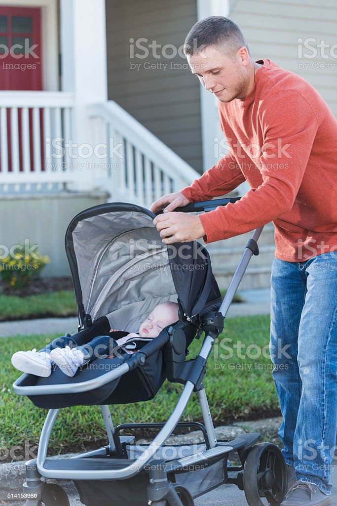 Father pushing his baby girl in stroller stock photo