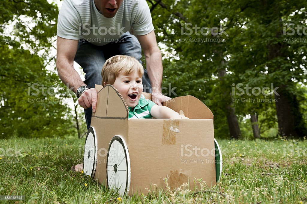 Father pushing his son in a cardboard box on grass stock photo