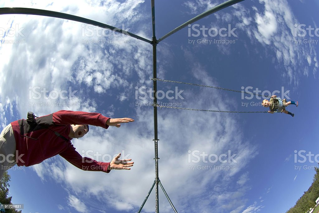father pushing son on swing royalty-free stock photo