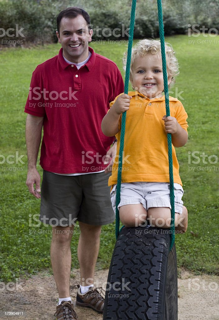 Father pushing toddler son on tire swing royalty-free stock photo