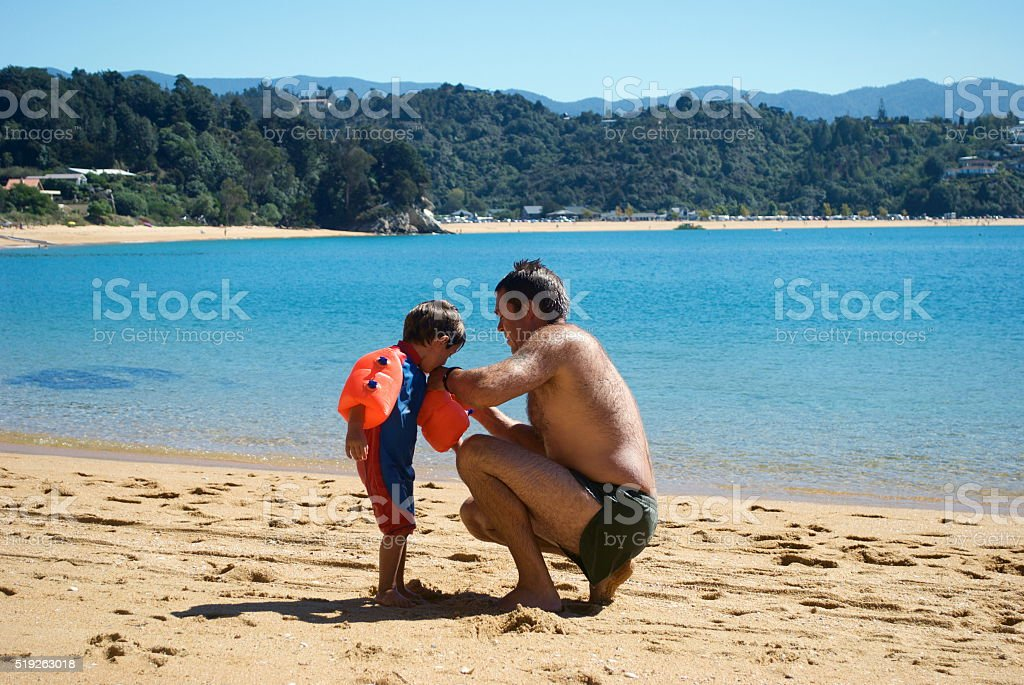 Father puts Arm Bands on his Son at Beach stock photo