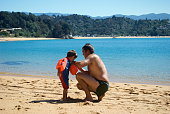 Father puts Arm Bands on his Son at Beach