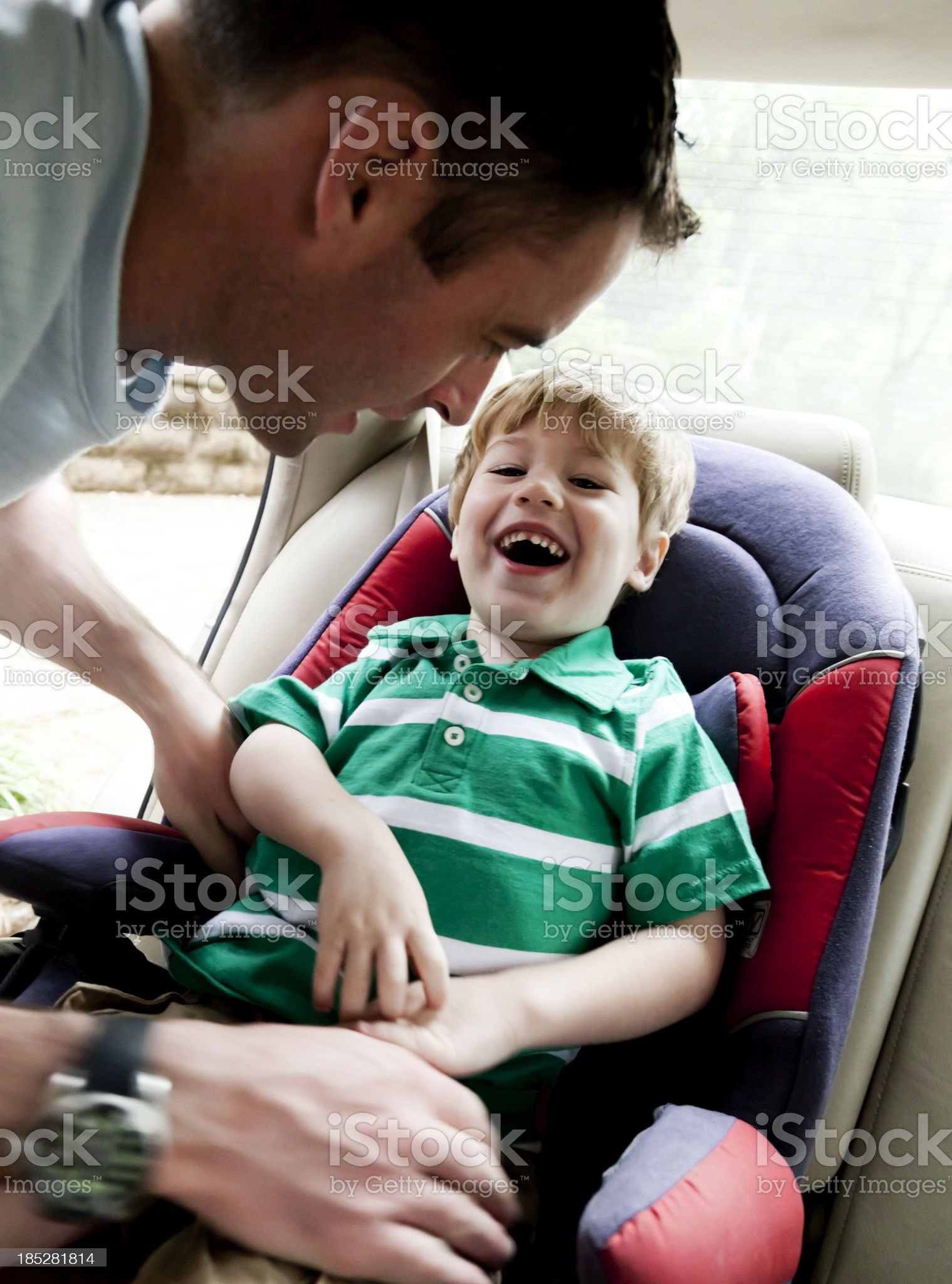 Father puts child in car seat royalty-free stock photo