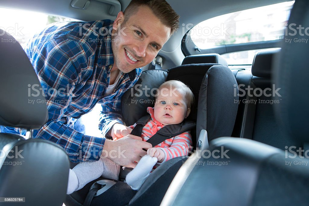 Father Putting Daughter In Safety Seat On Car Journey stock photo