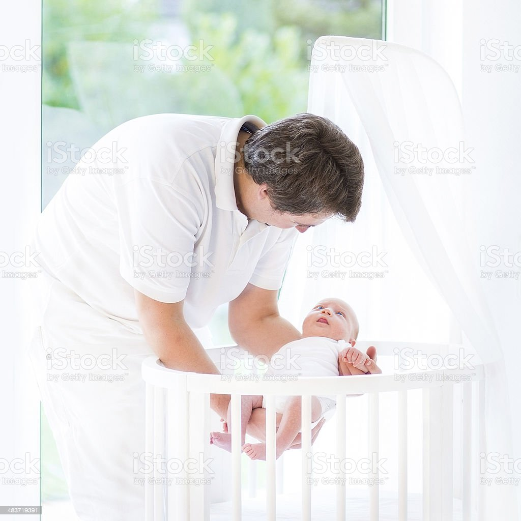 Father putting newborn baby in white round crib near window royalty-free stock photo
