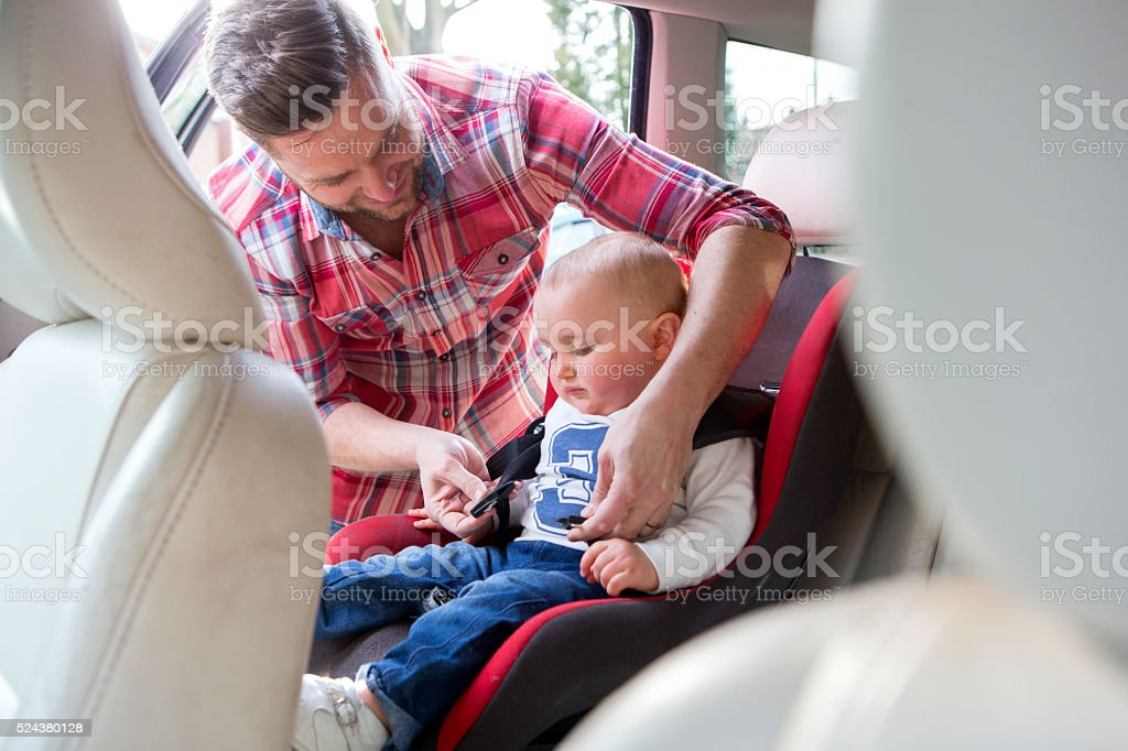 Father Putting Son In Safety Seat On Car Journey stock photo