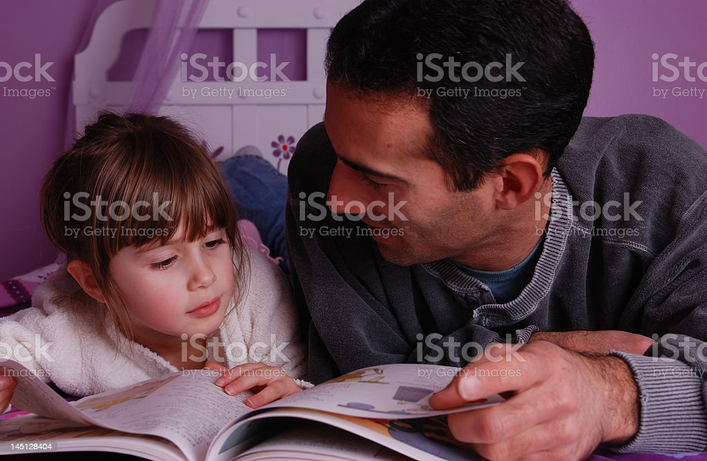 Father reading a bedtime story to his daughter royalty-free stock photo