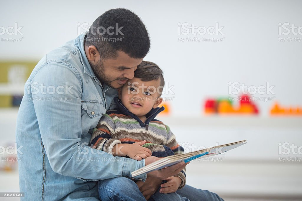 Father Reading a Book to His Son stock photo