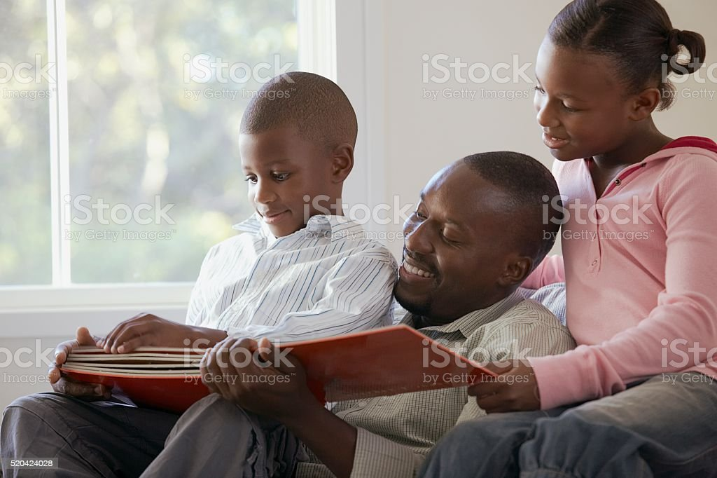 Father reading a storybook with his children stock photo