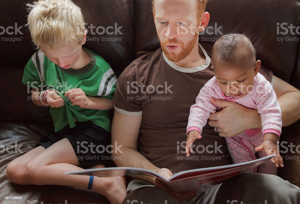 Father reading bedtime stories to his children. Multi-ethnic group stock photo