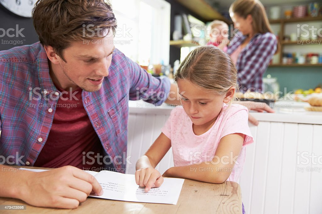Father Reading Book With Daughter At Kitchen Table stock photo