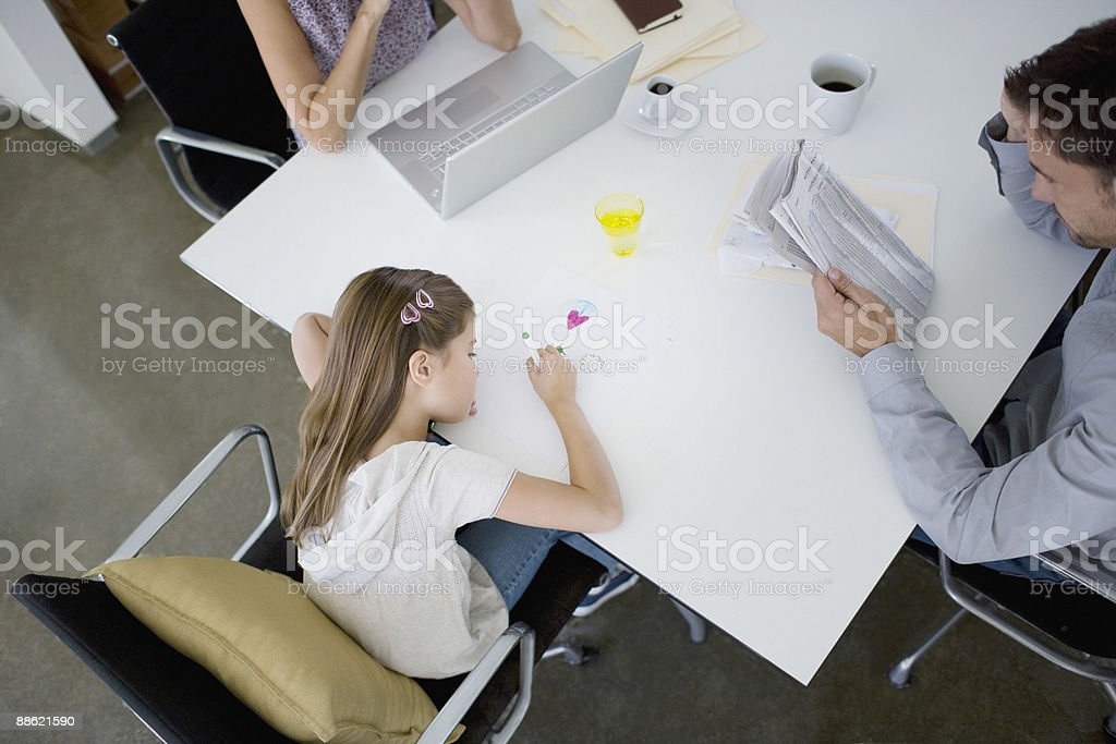 Father reading newspaper at table while daughter draws royalty-free stock photo