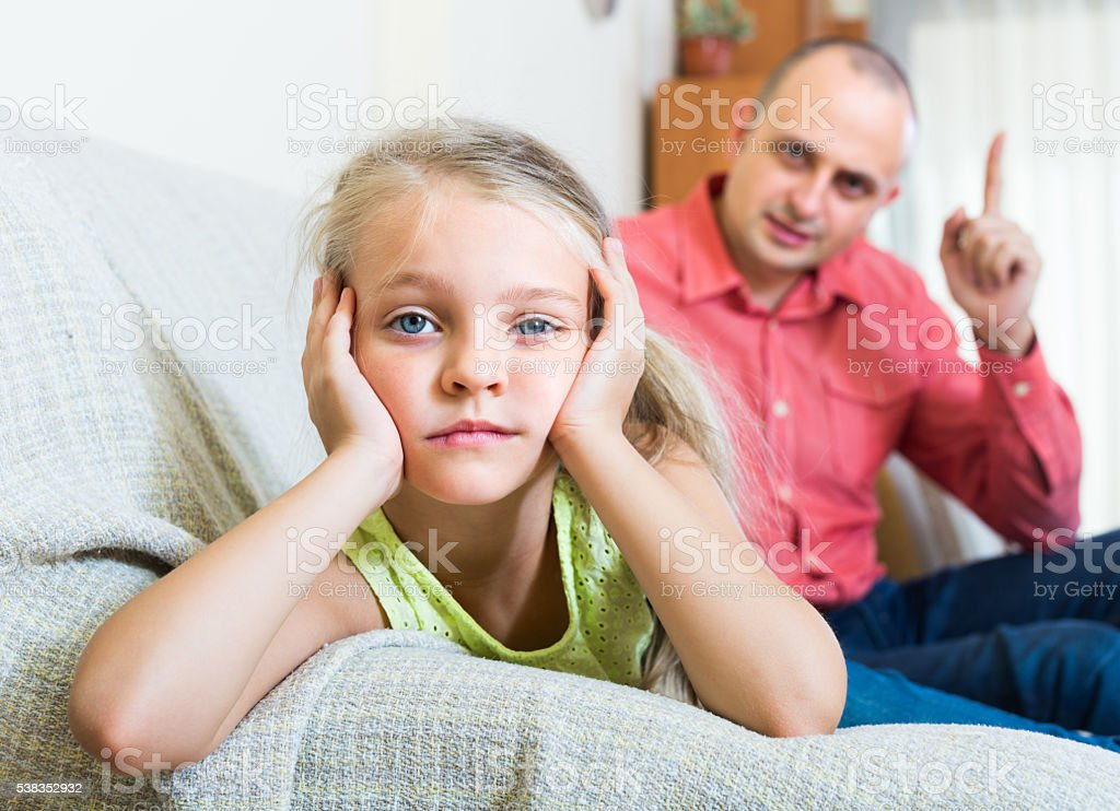 father rebuking  daughter for offence stock photo