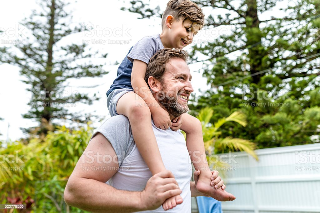 Father riding son on shoulder stock photo