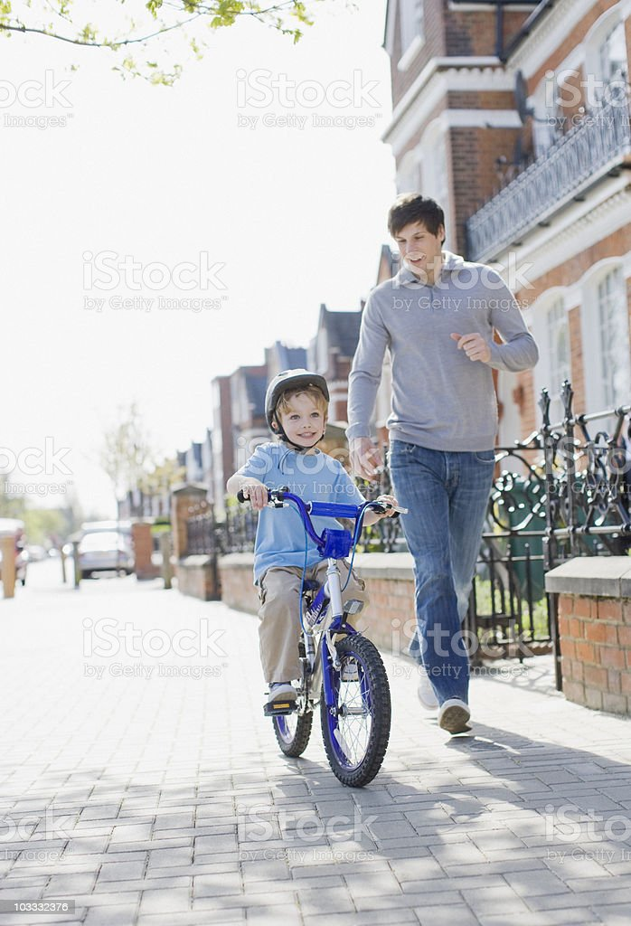Father running alongside son riding bicycle on sidewalk stock photo