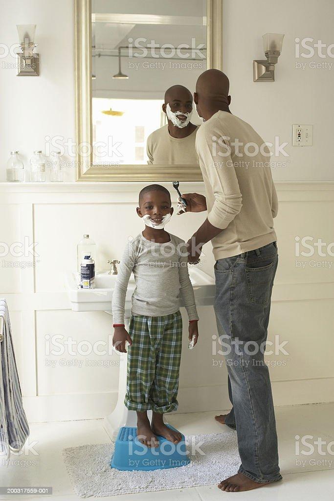 Father shaving by son (5-7) wearing shaving foam, portrait of boy stock photo