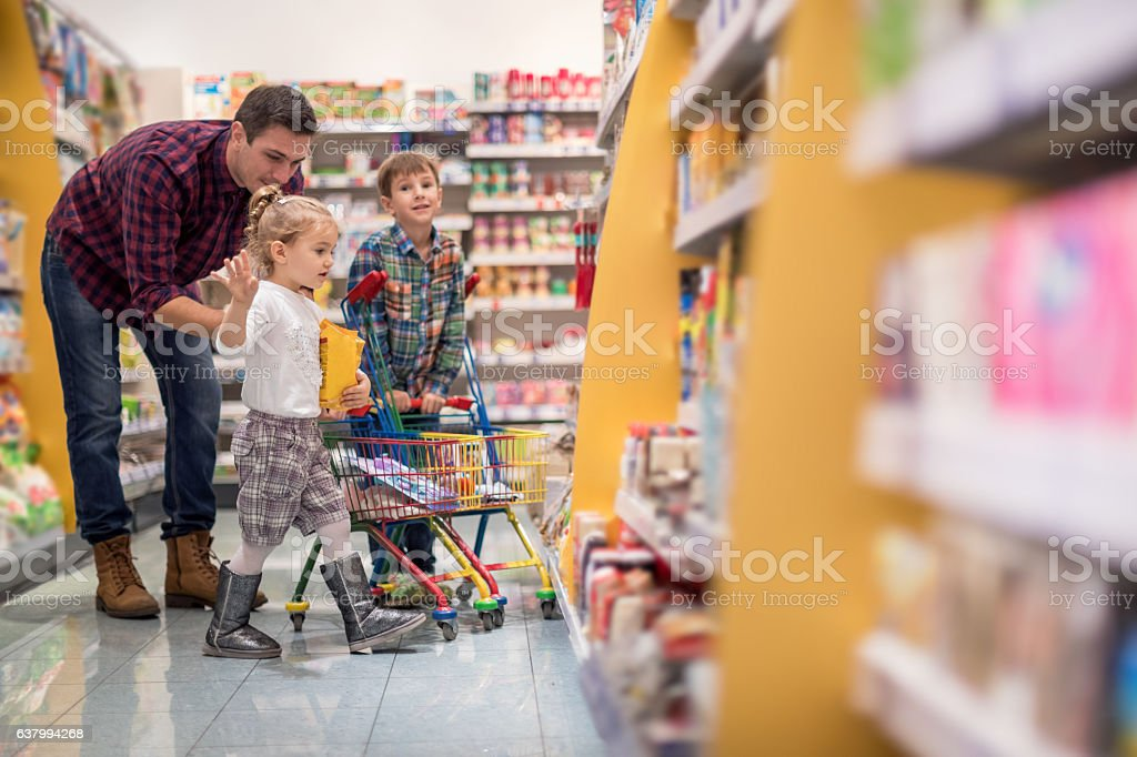 Father shopping with children at supermarket stock photo