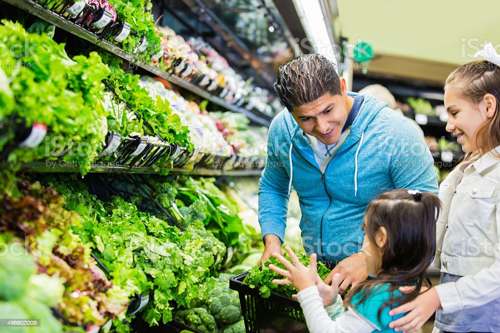 Father shopping with daughters for groceries in local supermarket stock photo