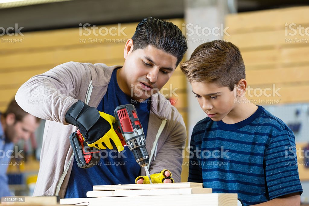 Father show son how to drill in local workshop stock photo