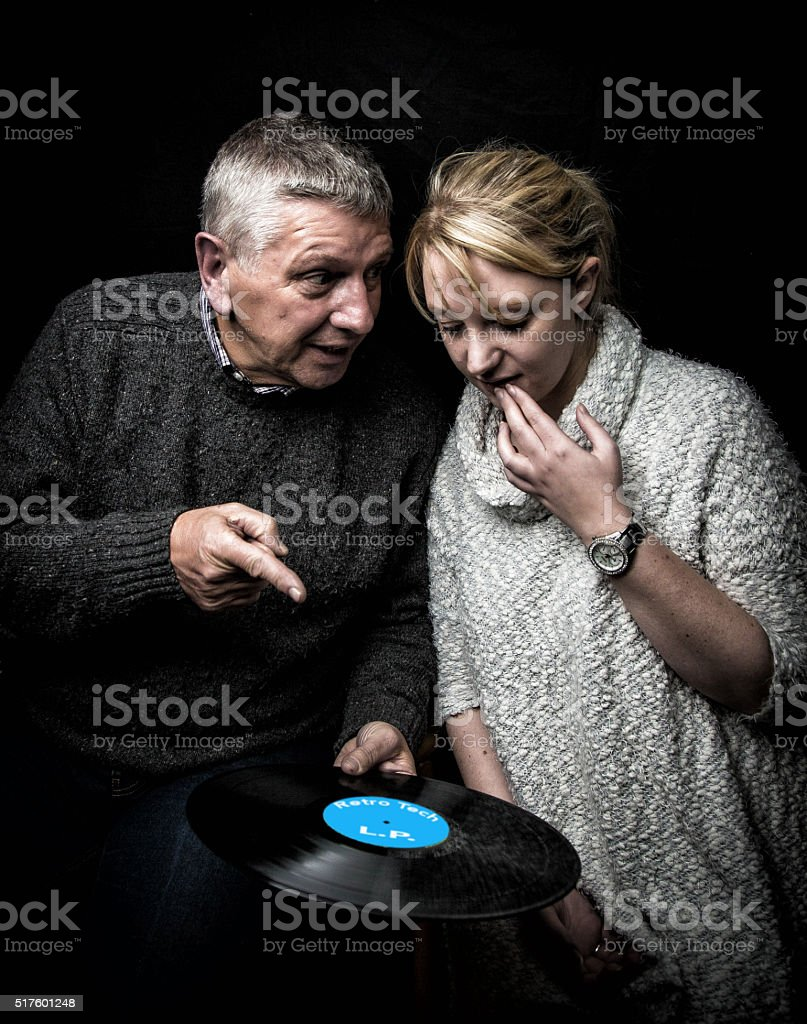 Father showing daughter a vinyl LP record stock photo