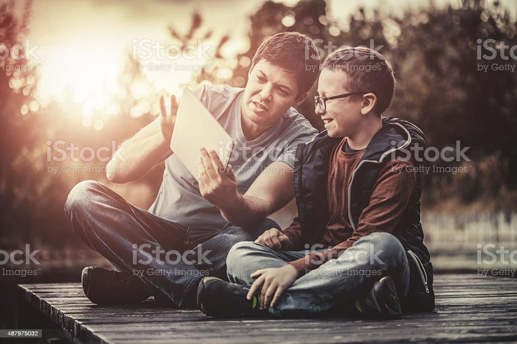 Father showing to his son how to use digital tablet stock photo