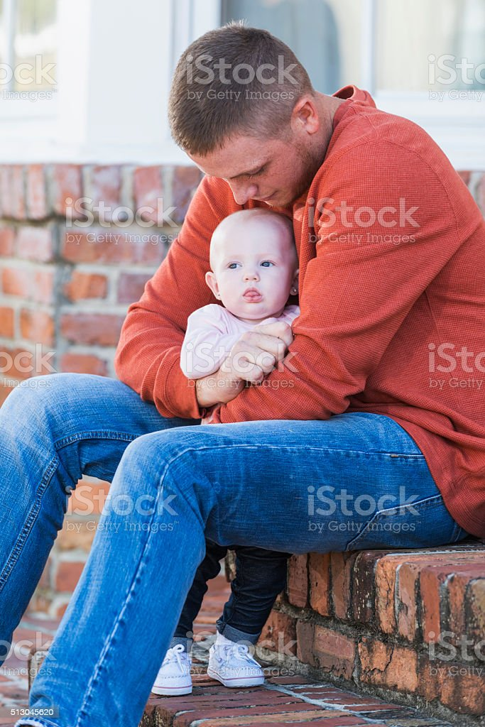 Father sitting on steps hugging baby girl stock photo