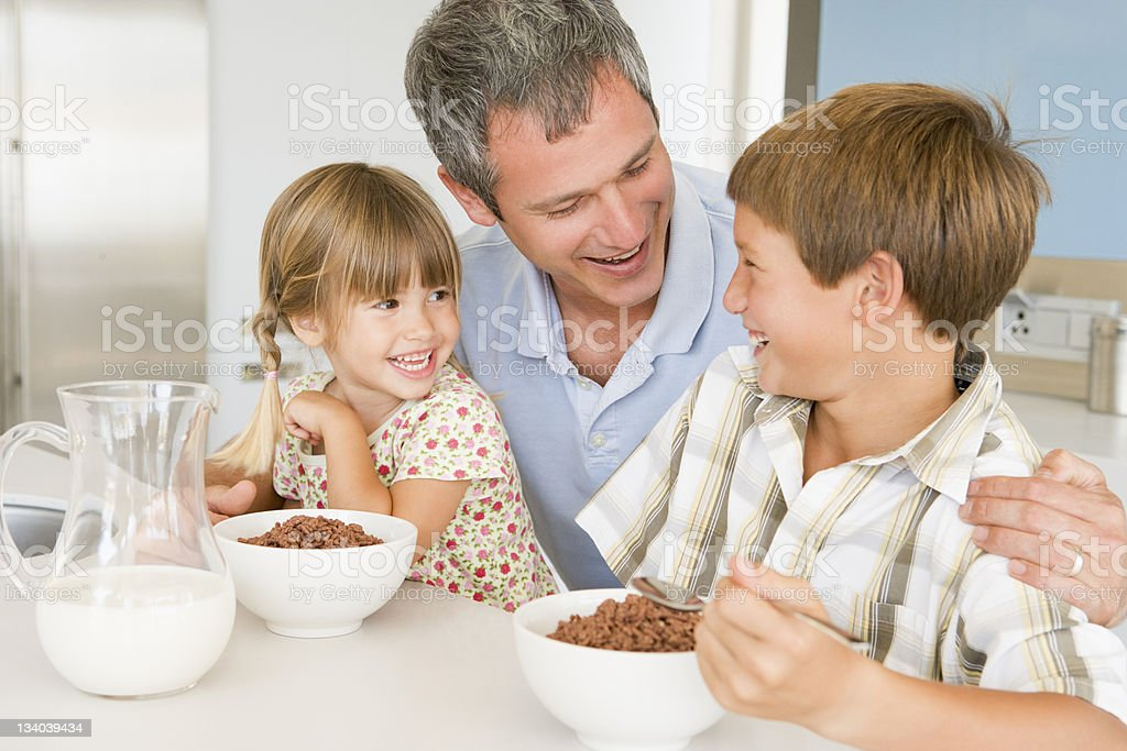 Father Sitting With Children As They Eat Breakfast royalty-free stock photo