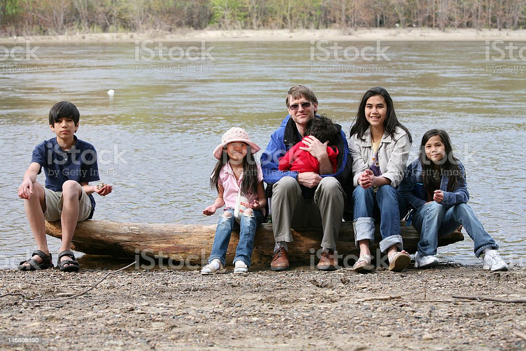 Father sitting with his children on fallen log royalty-free stock photo