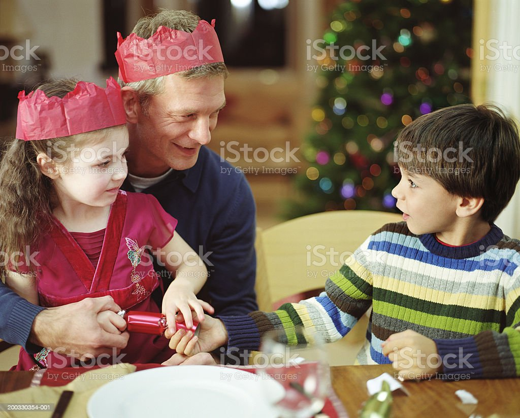 Father sitting with son and daughter (5-7) pulling cracker, smiling stock photo