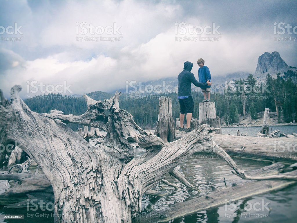 Father son day on a mountain lake during storm stock photo