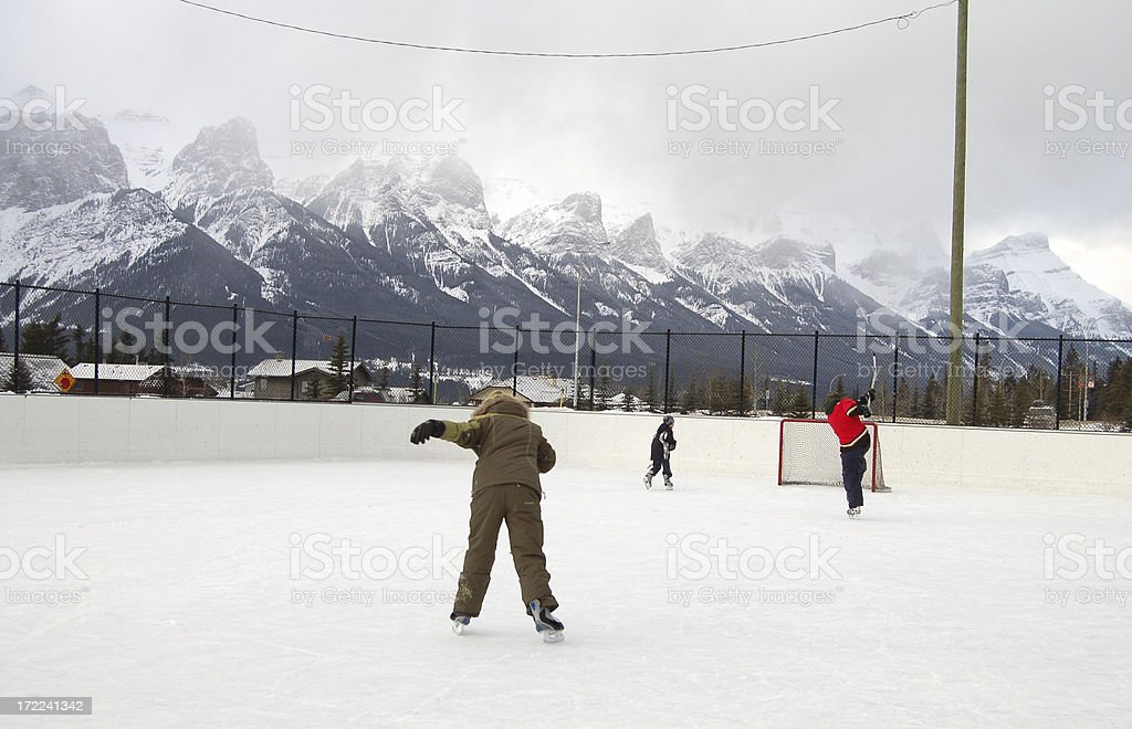 Father & Son play hockey while girl learns to skate royalty-free stock photo