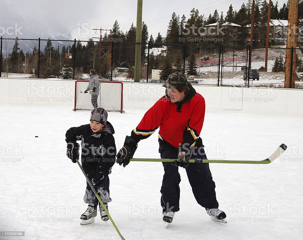 Father & son playing ice hockey on outdoor rink royalty-free stock photo