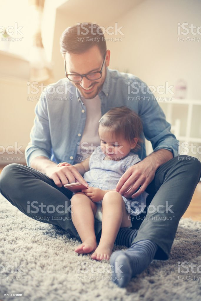 Father spending time at home with his little baby. stock photo