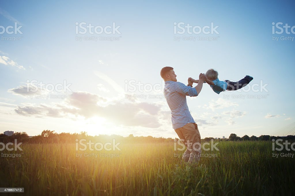 father spinning his son stock photo