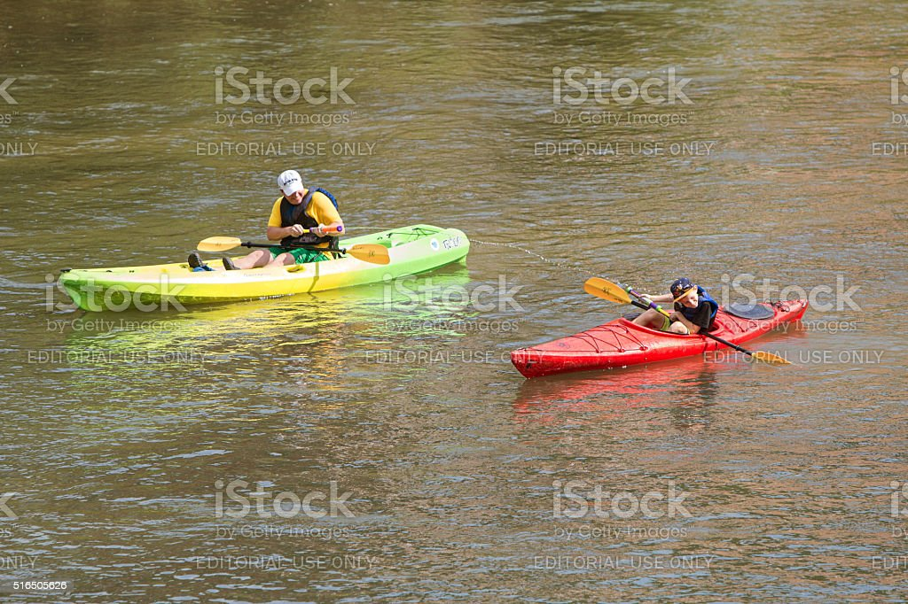 Father Squirts Son With Water Gun Kayaking Down Atlanta River stock photo